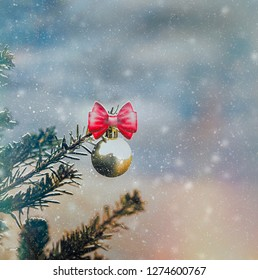 Gold Christmas ball hanging from pine  tree branch with snow background. Stock Image.