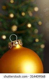 Gold Christmas ball ornament in front of a defocused Christmas tree with lots of shimmering lights, close up