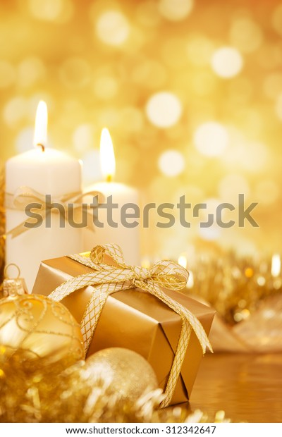 Gold Christmas baubles, candles and a gift on a bright glittering gold background.