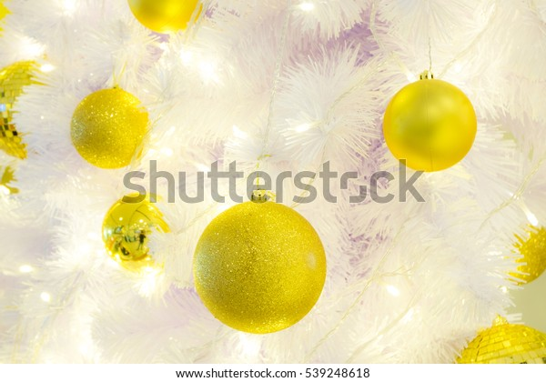 Gold christmas baubles on white chrismas tree.