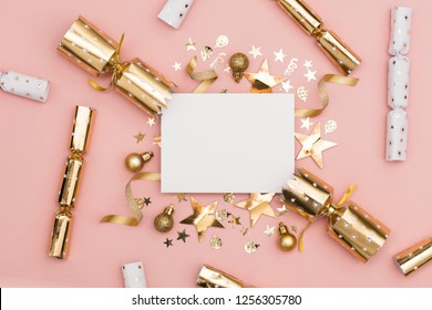 Gold Christmas cracker with a blank white label. luxury gold festive cracker on a pastel pink background