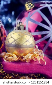 Gold Christmas decoration ornament for the Christmas tree surrounded by tinsels and  more Christmas decoration