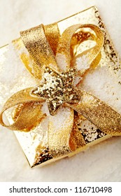 Gold Christmas gift box on the snow