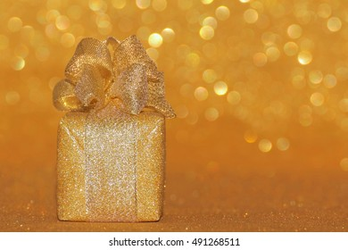 Gold Christmas glitter gift box or present  with  golden bow and ribbon on golden bokeh  background.   Christmas,  new year, birthday, celebration, anniversary concept.