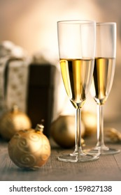 Gold Christmas ornaments in front of a brown Christmas present together with two champagne flutes.
