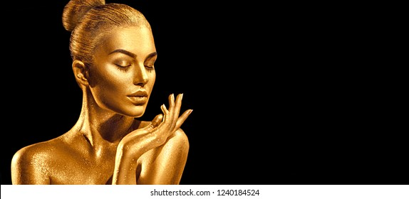 Gold Christmas Woman. Beauty fashion model girl with Golden make up, hair and jewellery, pointing hand on black background. Gold glowing skin. Metallic, glance Fashion art portrait, Hairstyle, make up