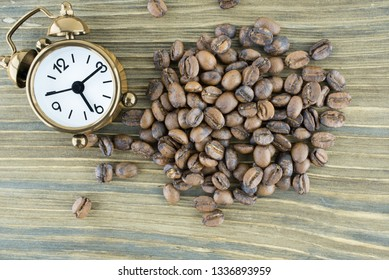 Gold clock and coffee beans on wooden background - macro photo.