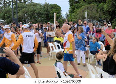 Gold Coast 2018 Commonwealth Games Queens Baton Bearer in Coffs Harbour Australia as on 1 Feb 2018. Spectators looking while baton or torch bearer carries the baton