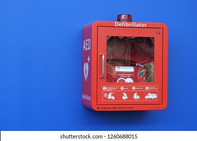 GOLD COAST, AUS - DEC 10 2018:Red Box Defibrillator Cabinet on a blue wall.Each year around 30,000 people in australia are struck by sudden cardiac arrest outside of hospital environments.
