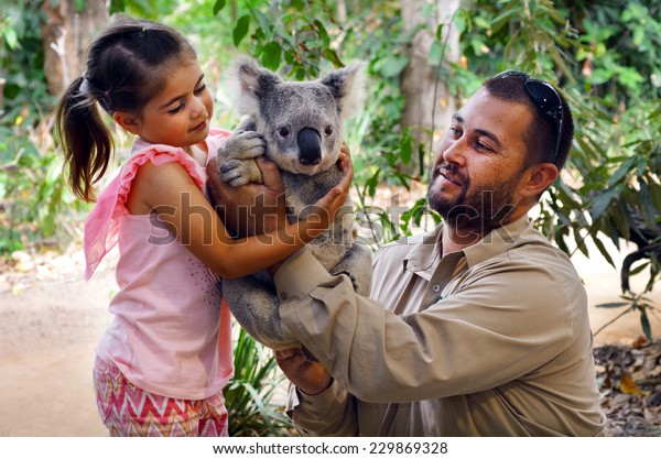 GOLD COAST, AUS - NOV 04 2014:Young girl (Talya Ben-Ari age 05) holding a Koala with Zookeeper in Currumbin Wildlife Sanctuary Gold Coast Queensland, Australia.Koalas cannot be kept legally as pets.
