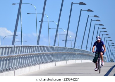 GOLD COAST, AUS - OCT 13 2014:Man riding a bike over Sundale Bridge. The bridge span across the Nerang River in Southport Gold Coast Queensland Australia.