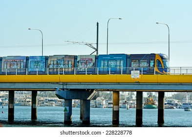 GOLD COAST, AUS - OCT 29 2014:Gold Coast Light Rail G cross over Sundale Bridge and Southport skyline in Gold Coast Queensland, Australia.The line opened on July 2014 and it 13 Km (8.1 mi) long.