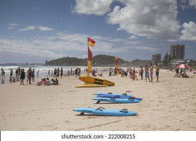 GOLD COAST, AUSTRALIA - 11 JANUARY 2014 - A busy beach in Queensland showing swimmers and junior surf lifesavers meeting to compete.  Crowds must swim in a safe area between the yellow and red flags.