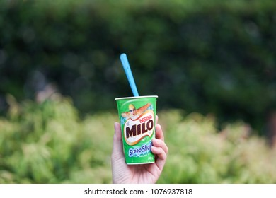 Gold Coast, Australia - April 17, 2018 : A photo of a lady's hand holding up a cup of Milo Scoop Shake chocolate ice cream. Milo brand belongs to Nestle. Editorial use only.