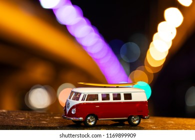 GOLD COAST, AUSTRALIA - AUGUST 11 2018: Minature kombi with surfboard on top with bokeh citylights in the background
