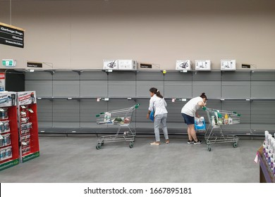 Gold Coast, Australia - March 9, 2020: Supermarket empty toilet paper shelves amid coronavirus fears, shoppers panic buying and stockpiling toilet paper preparing for a pandemic