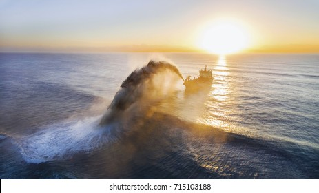 GOLD COAST, AUSTRALIA - SEPTEMBER 10 2017: Aerial silhouette view at sunrise, of the Balder R dredger pumping sand towards Surfers Paradise coastline to replenish the beaches.