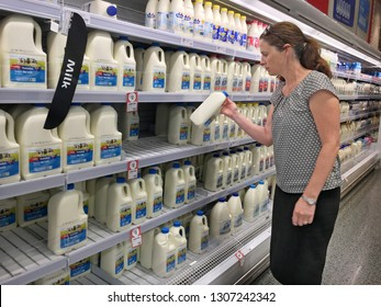 GOLD COAST - JAN 29 2019:Woman buys Australian milk in a supermarket. Australian dairy farmers produce 9,102 million litres of whole milk per year with  value of milk production being $4 billion.