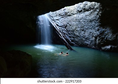 GOLD COAST - OCT 06 2014:Couple swim in Natural Bridge at Springbrook National Park in Queensland Australia.It's a World Heritage Rainforest featuring many waterfalls, trees and fascinating wildlife.