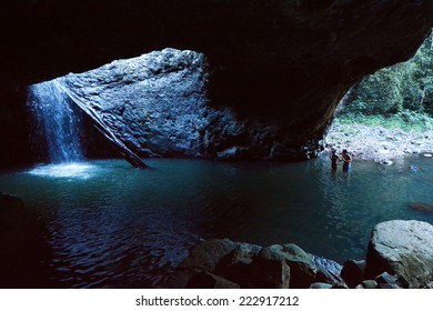 GOLD COAST - OCT 06 2014:Couple in Natural Bridge at Springbrook National Park in Queensland Australia.It's a World Heritage Rainforest featuring many waterfalls, trees and fascinating wildlife.