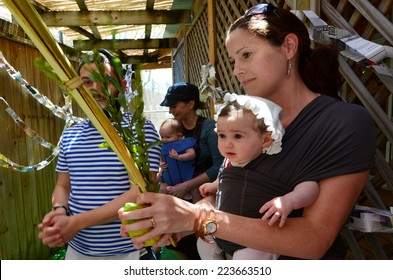 GOLD COAST - OCT 12 2014:Jewish people blessing on the four species in a Sukkah on Sukkot Jewish Holiday.There are about 100,000 Jewish Australians they are 0.3 percent of the Australian population.