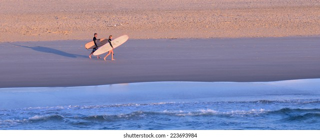 GOLD COAST - OCT 13 2014: Man and woman surfers with surfing boards  walks along the Spit beach.It is a very popular surfing beach in Surfers Paradise Gold Coast Queensland, Australia.