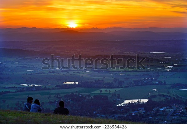 GOLD COAST- OCT 20 2014: Young travelers looks at the sunset from Mount Tamborine in Gold Coast Queensland, Australia.