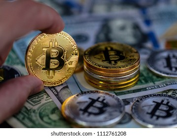 Gold coin of bitcoin in hand. Symbolic coins of bitcoin on banknotes of one hundred dollars. Exchange bitcoin cash for a dollar.