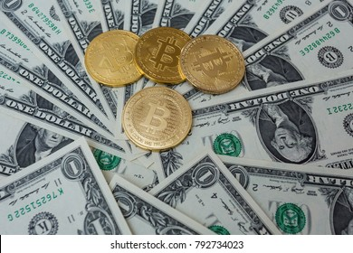 Gold coins of bitcoin on the banknotes of dollars.