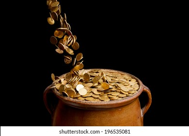 gold coins falling in the vintage pot isolated on black background