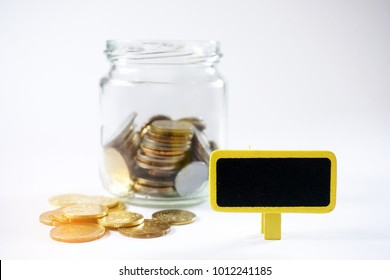Gold coins in glass jar with mini chalkboard with selective focus. Finance concept