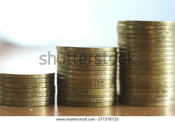 gold coins on the table. close-up with blurred bokeh background, UAH Ukrainian hryvnia