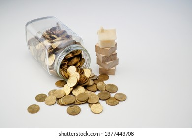 Gold coins spilling out of a jar and a tiny house miniature isolated on white background