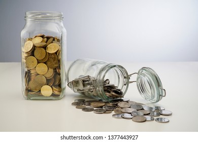 Gold coins spilling out of a jar isolated on white background
