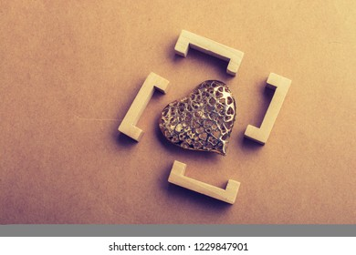 Gold color heart shaped  decorative object in brackets in view