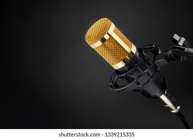 Gold colored condenser microphone other black background. Sound recording equipment.
