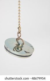 Gold colored metal bath plug hanging from a chain