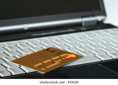 Gold Credit Card atop a Notebook
