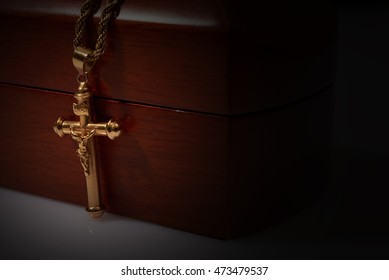 gold cross and chain top on a wooden box