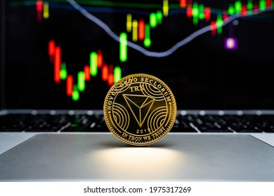Gold cryptocurrency coin - TRON coin is placed on a laptop with a graph background in the computer screen.