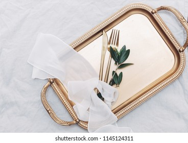 Gold cutlery on tray. Festive Place Setting