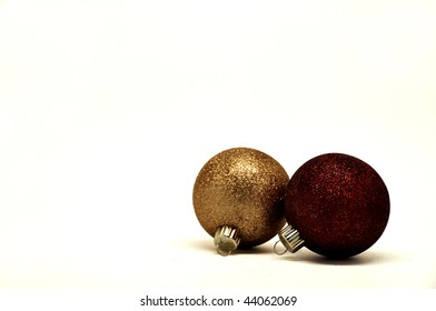 a gold and dark red christmas ornaments isolated over a white background