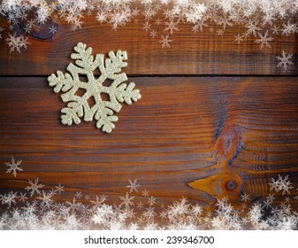 Gold decoration snowflake on a wooden background