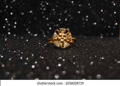Gold and diamond ring on black sparkle background