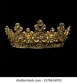 A gold and diamond royal crown on black blackground