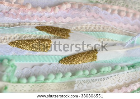 Gold Dipped Glitter Goose Feathers Laying On Pink Peach Mint Blue Laces Vintage Ribbons And Pom
