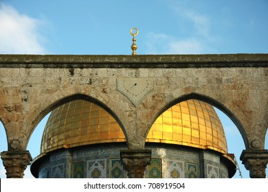 gold dome and arches Israel, Jerusalem: a mosque Dome of the Rock and a light vaulted arch. golden dome, blue sky.  on the arch a sundial