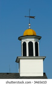 Gold dome church steeple with a weather vane and lightning rods with blue sky in background