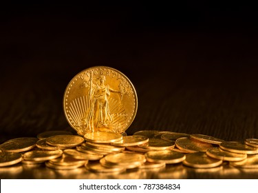 Gold Eagle one ounce coin against a golden background of other coins with focus on the Liberty symbol