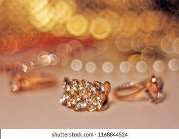 Gold earring with diamonds and bokeh lying on white table